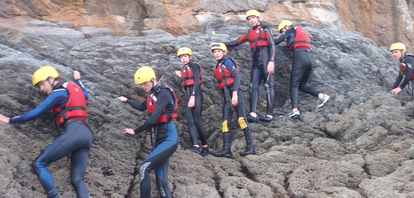 People climbing along the side of a cliff